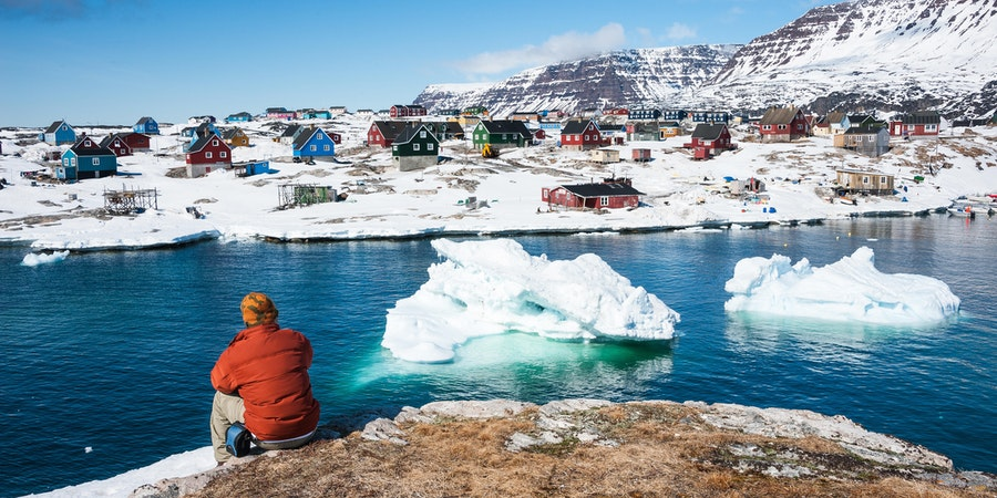 Man Enjoying the View of Qeqertarsuaq, a Small Town of Greenland in Early Spring Time (Photo: Yongyut Kumsri/Shutterstock)