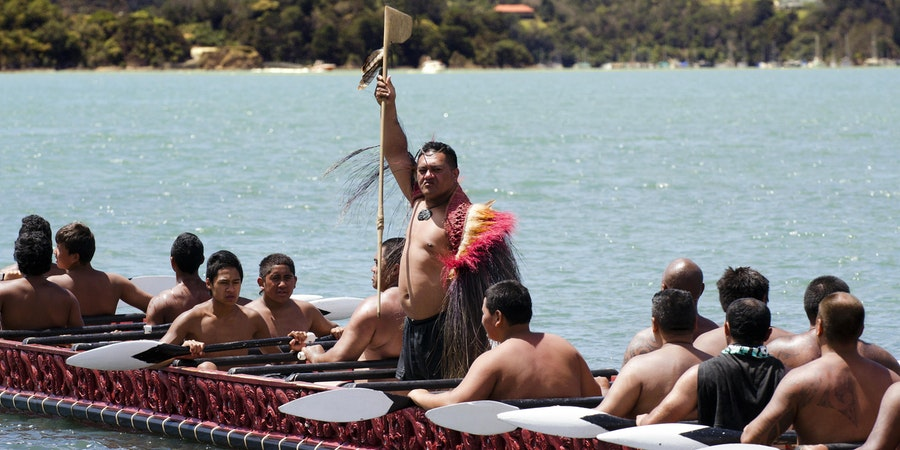Maori Chief and Warriors row War Canoe During Waitangi Day (Photo: ChameleonsEye/Shutterstock)