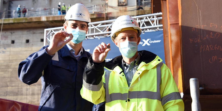 "Tobias King, Celebrity Cruises' Edge Series Project Manager, and Sébastien Le Boulluec, Chantiers de l'Atlantique's Edge Series Project Manager, hold the ceremonial ""good fortune"" coin for Celebrity Beyond as the ship's keel is laid (Photo: Celebrity Crui"