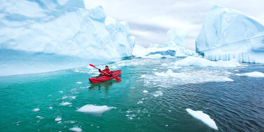 Man Kayaking Near the Icebergs in Antarctica (Photo: Song_about_summer/Shutterstock)